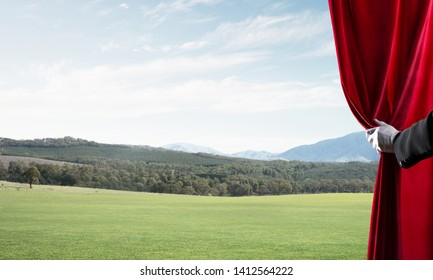 Human hand in glove opens red velvet curtain to landscape