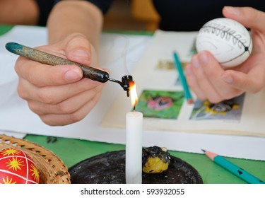 A human hand is heating a stylus with wax near the flame of the candle burning. Another hand is holding a white egg with traditional pattern.