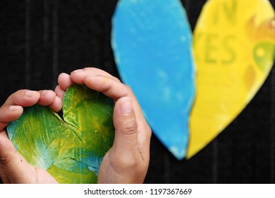 Human hand hold heart in hands with another at bottom, two hearts in yellow and blue color with thank you message