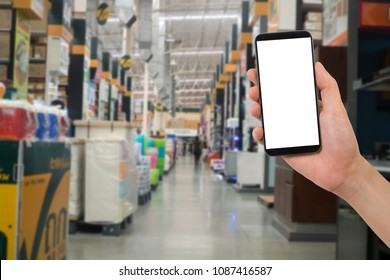 human hand hold smartphone, tablet, cell phone on blurry storehouse, shelf of products, concept of Ordering product online.