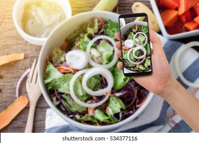 human hand hold smartphone, tablet, cell phone on blurry kitchen table with vegetable salad and dressing, concept of diet food, take a photo vegetable salad on screen cell phone.