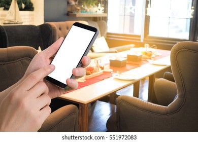human hand hold smartphone, tablet, cell phone with blank screen on blurry restaurant  background. booking online concept.