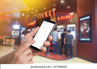 human hand hold and touch smartphone, tablet, cell phone with blank screen on blurry theater, Online booking ticket concept.