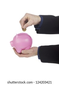 Human hand holding coin over pink piggy bank against white background