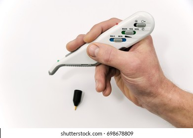 The human hand is holding the device for Electro Acupuncture on a white background.