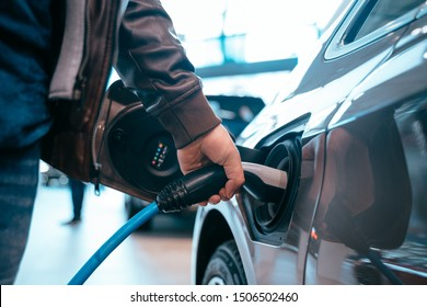 Human hand is holding Electric Car Charging connect to Electric car - Shutterstock ID 1506502460