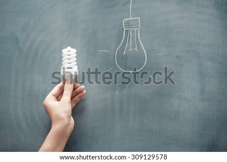 Human hand holding energy saving lamp at the blackboard