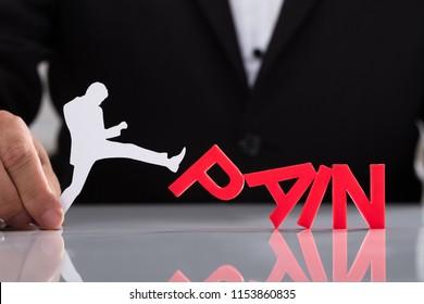 Human hand holding human figure kicking red pain word on reflective desk