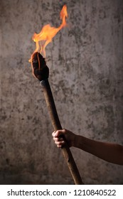 Human hand holding a flaaming torch
