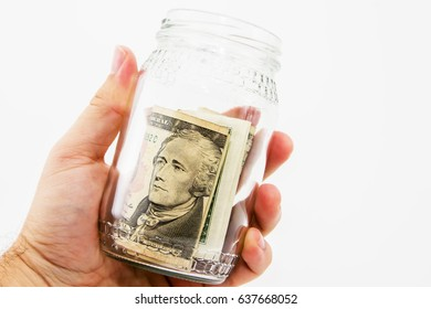 A human hand holding a glass savings jar with USA dollar bills inside. This image also has a plain background.