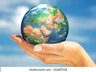 Human hand holding a globe. Elements of this image furnished by NASA.