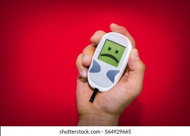 Human hand holding glucometer on red background with sad face on its monitor illustrating bad blood sugar levels. Diabetes concept
