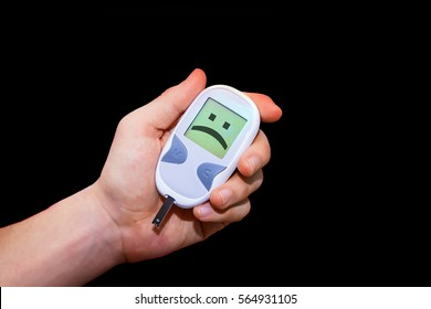 Human hand holding glucometer on black background with sad face on its monitor illustrating bad blood sugar levels. Diabetes concept