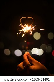 Human hand holding heart shaped igniting sparklers with bokeh on black background