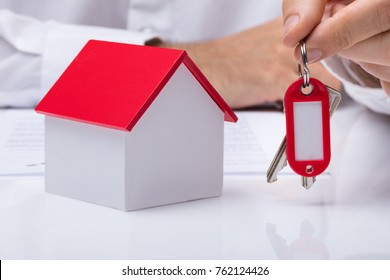 Human Hand Holding House Keys With House Model On Desk