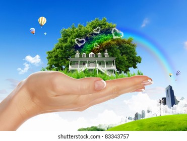 Human hand holding houses surrounded by nature against blue sky and rainbow
