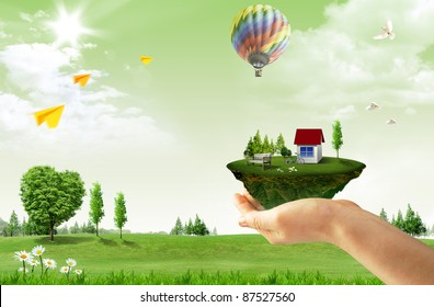 Human hand holding houses surrounded by nature