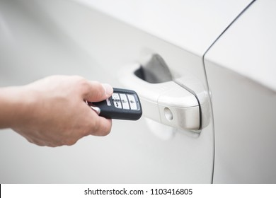 Human hand holding a keyless entry device or key fob to open the new car and start the car. focus on the keyless device system and door handle