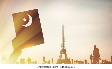 Human hand holding a Koran with parisian Eiffel tower on background.