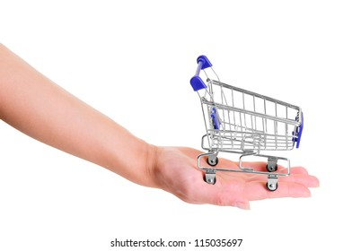 human hand holding layout of blue shopping cart.  isolated on white background. close-up