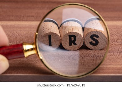 Human Hand Holding Magnifying Glass Over Wooden Cork With IRS Text On Wooden Textured