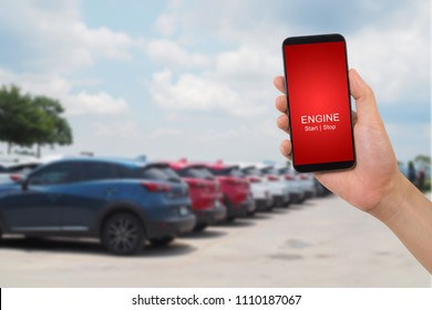 human hand holding mobile on blurry car background.