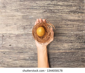 Human hand holding the nest with easter eggs over wooden table background. Happy Easter