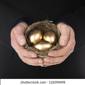 Human hand holding a nest with three golden eggs inside