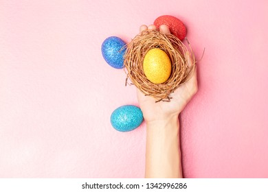 Human hand holding the nest with yellow easter egg and colorful easter eggs on pink color background. Happy Easter