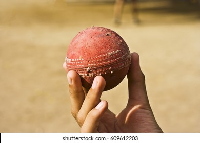 Human hand holding old cricket ball.