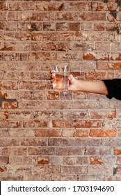 Human hand holding out a glass of water, isolated against a brick wall background