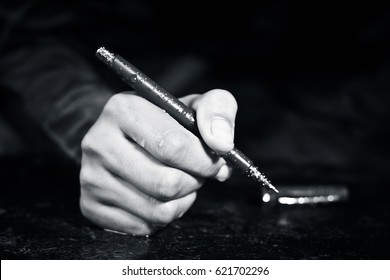 human hand holding pen with dark black background