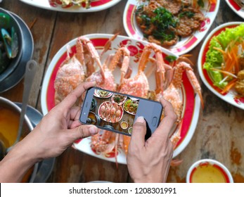Human hand holding a smartphone photographing food