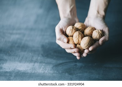human hand holding walnuts on dark blue background