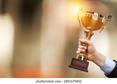 Die menschliche Hand hält den Meister der goldenen Trophäe. Erfolgskonzept.