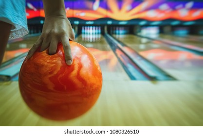 The human hand holds an orange bowling ball ready to throw it forward.