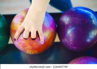 The human hand holds an orange bowling ball. Vivid colors. Summer day,