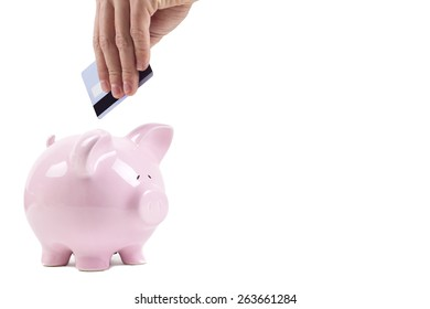 human hand insert credit card in to piggy bank isolated on white background