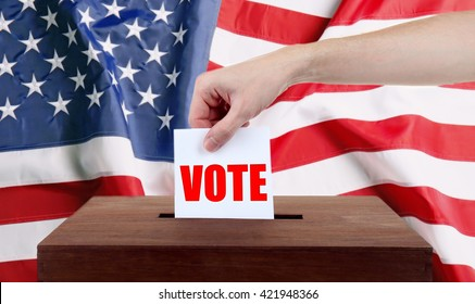 Human hand inserting bulletin in ballot box on USA National Flag background