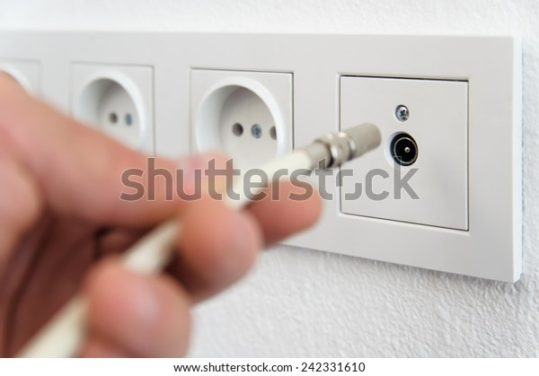 Human hand inserts the antenna cable to the TV outlet