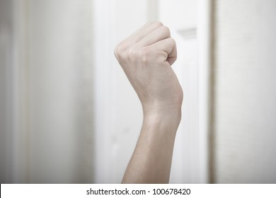 Human hand knocking at the wooden door