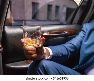Human hand in the limousine holding glass of wiskey. Front closeup view