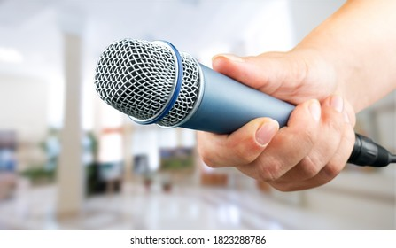 Human hand with a microphone on blur  background