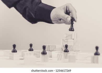 A human hand moving King chess piece at table. Selective focus