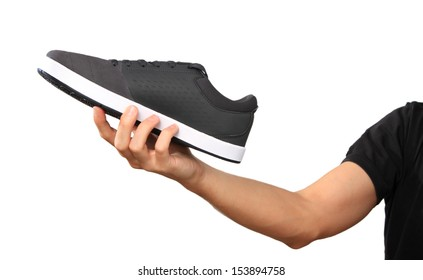 Human Hand with a new sport shoe / sneakers, isolated on white background. All logos and brand markings have been removed.