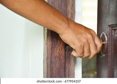 Human hand opens the door.