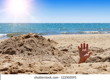 Human hand out of the hole on the sandy beach