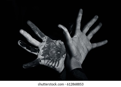 Human hand painted with poster color, emerging from darkness.