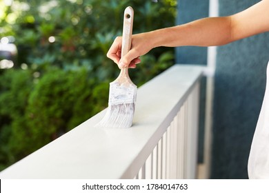 Human hand painting a house deck handrail, doing home improvement by refreshing the paint of the wooden structure at the house entry. Fresh wet white paint.