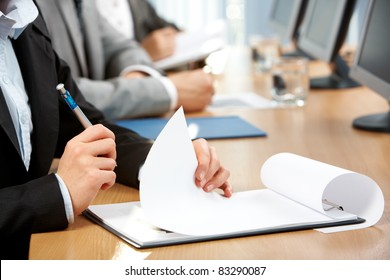 Human hand with pen holding paper during written work